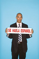 African American man holding sign reading se against blue background