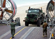 Navy load master guides Marine 7_ton truck onto Landing Craft, Air Cushioned LCACs