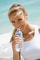Caucasian young adult woman drinking water on beach