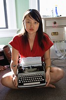 Pretty Asian young woman sitting on floor in red robe holding typewriter