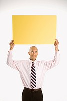 African American man holding blank yellow sign overhead standing against white background
