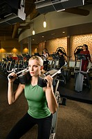 Prime adult Caucasian female using exercise equipment at gym