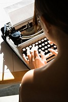 Back view of nude young Asian woman sitting at kitchen table typing on typewriter