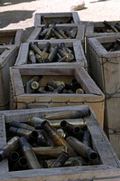 Spent .50_caliber machine gun shell casings sit inside wooden boxes