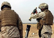 Marine prepares to drop a high explosive round into the tube