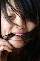 Close up portrait of pretty young Asian woman biting her hair