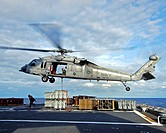 An MH_60S Seahawk helicopter prepares to deliver ammunition to flight deck