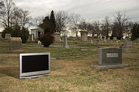 Flat panel television set in cemetary next to headstone