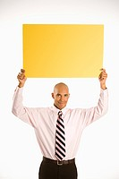 man holding blank yellow sign overhead standing against white background.