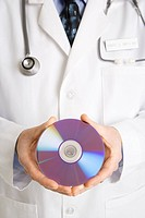 Close up of Caucasian mid adult male physician holding compact disc