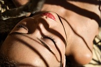 Pretty Filipino bare young woman lying on beach with shadows  (thumbnail)