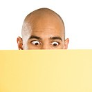 African American man peeking over blank yellow sign