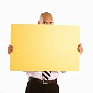 African American man holding and peeking over blank yellow sign