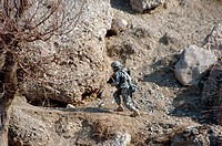 U.S. Army soldier walks up the side of a hill to look at caves