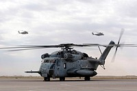 Two CH_53E Super Stallion helicopters with fly away as another prepares to depart