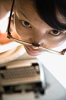 Young Asian woman making eye contact over eyeglasses with typewriter in background