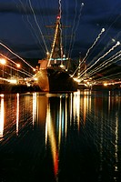 Holiday lights shine from guided_missile destroyer as she sits moored pier side