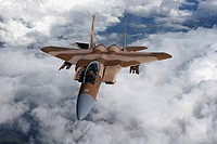 An F_15C Aggressor flies over a mountain range on a refueling mission