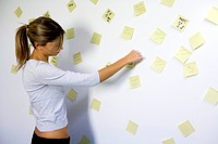 woman sticking memo notes on wall