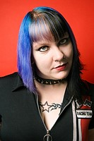 Portrait of Caucasian woman with blue hair, tattoo, and spike collar against orange background