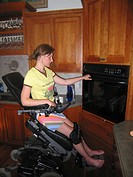 Young woman (electric wheelchair user) opens oven in her accessible kitchen.