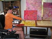 Female artist (wheelchair user) works with oils in her studio.