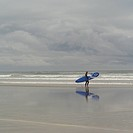 Surfer with surfboard on beach, Pacific Rim Park, Vancouver Island, Canada