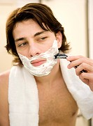 Close_up of young man looking at the mirror and shaving
