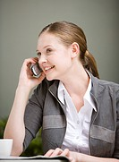 Close_up of businesswoman holding mobile phone and smiling happily