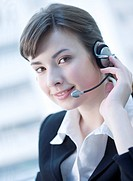Close_up of businesswoman wearing headphone and looking at the camera