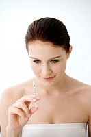 Portrait of young woman looking at syringe