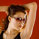 Portrait of young woman wearing sunglasses, posing with arms raising up