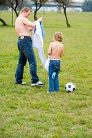 Father and son taking off their shirts together, rear view
