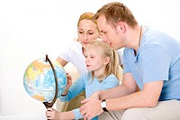 Parents with daughter looking at desktop globe, concentrating