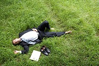 One mid adult man lying on lawn, laptop and dress shoes aside