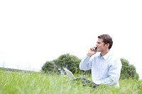 One mid adult man sitting on grass on the phone