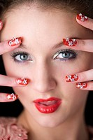Studio shot of teenage girl with makeup and artificial fingernails