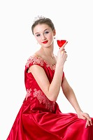 Teenage girl in formal dress holding a glass of wine