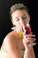 Teenage girl wearing formal dress holding a glass of wine