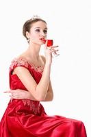 Teenage girl in formal dress drinking red wine