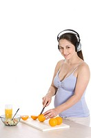 Pregnant young woman with headphones on, cutting an orange
