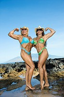 Pretty Caucasian mid adult women bodybuilders in bikinis standing and flexing biceps on beach.