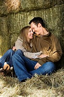 couple sitting on hay hugging and smiling at each other.