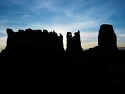 Sandstone mesas and buttes silhouetted in Monument Valley.