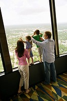 Caucasian family looking out observation deck at Tower of the Americas in San Antonio, Texas.