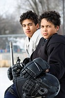 Two boys in ice hockey uniforms sitting on ice rink sidelines looking