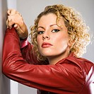 Woman in red jacket with arms raised leaning on wall
