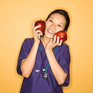 Asian Chinese mid-adult female doctor holding two red apples up to face against yellow background smiling and looking at viewer.