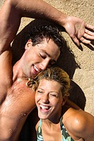 Smiling happy couple lying in sand on Maui, Hawaii beach.