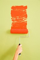 Hand painting a green wall with a red paint roller